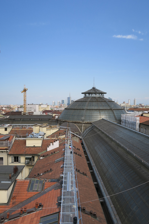 La passerella -work in progress- dei camminamenti sui tetti della Galleria Vittorio Emanuele II a Milano, dietro la cupola si intravedono i grattacieli di Porta Nuova | ©Sandra Longinotti