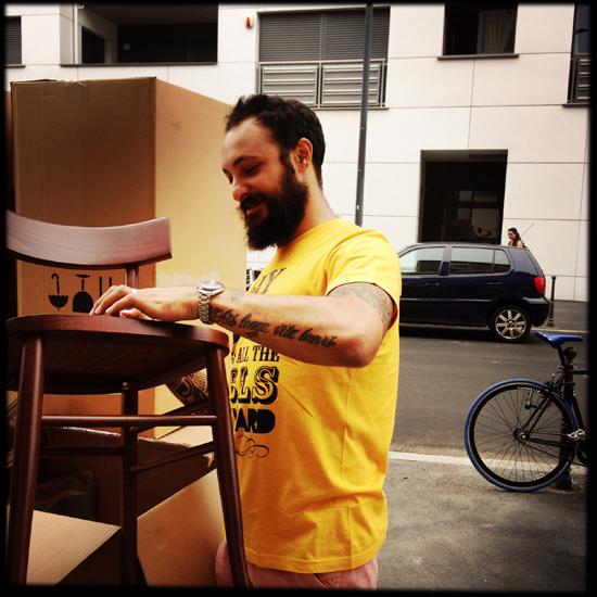 lo chef Diego Rossi estrae dallo scatolone la prima sedia di Trippa Milano | ©Sandra Longinotti